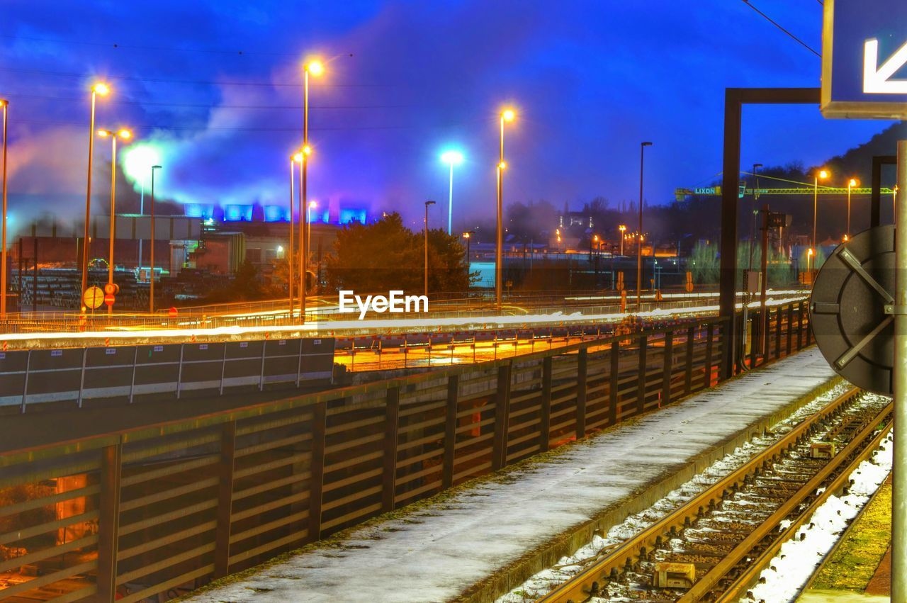 Railroad tracks by light trails and illuminated street lights against cloudy sky