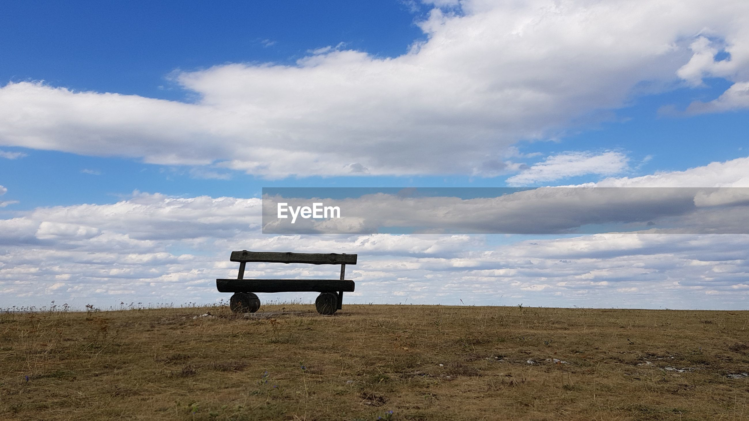 EMPTY BENCH ON FIELD BY ROAD AGAINST SKY