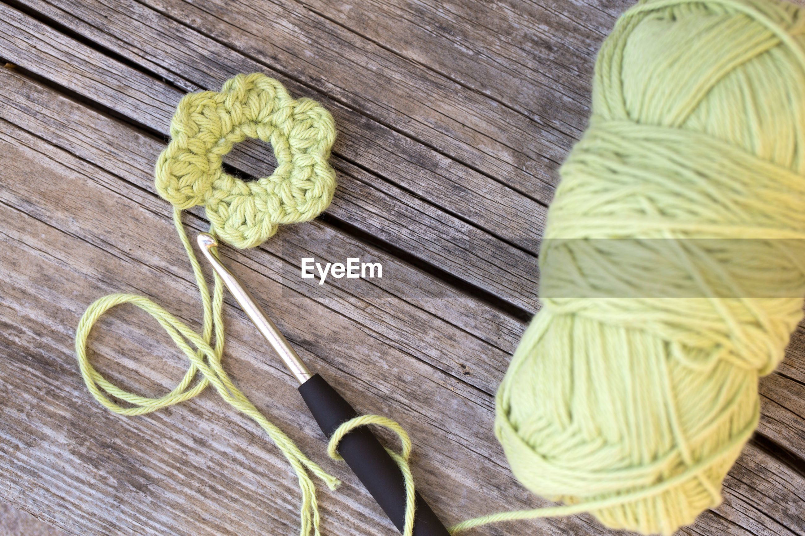 High angle view of wool with flower on table