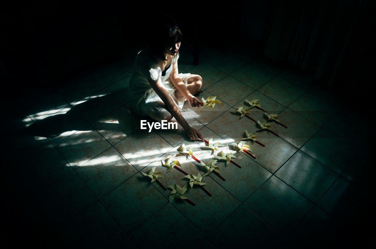 High angle view of woman arranging pinwheel on floor