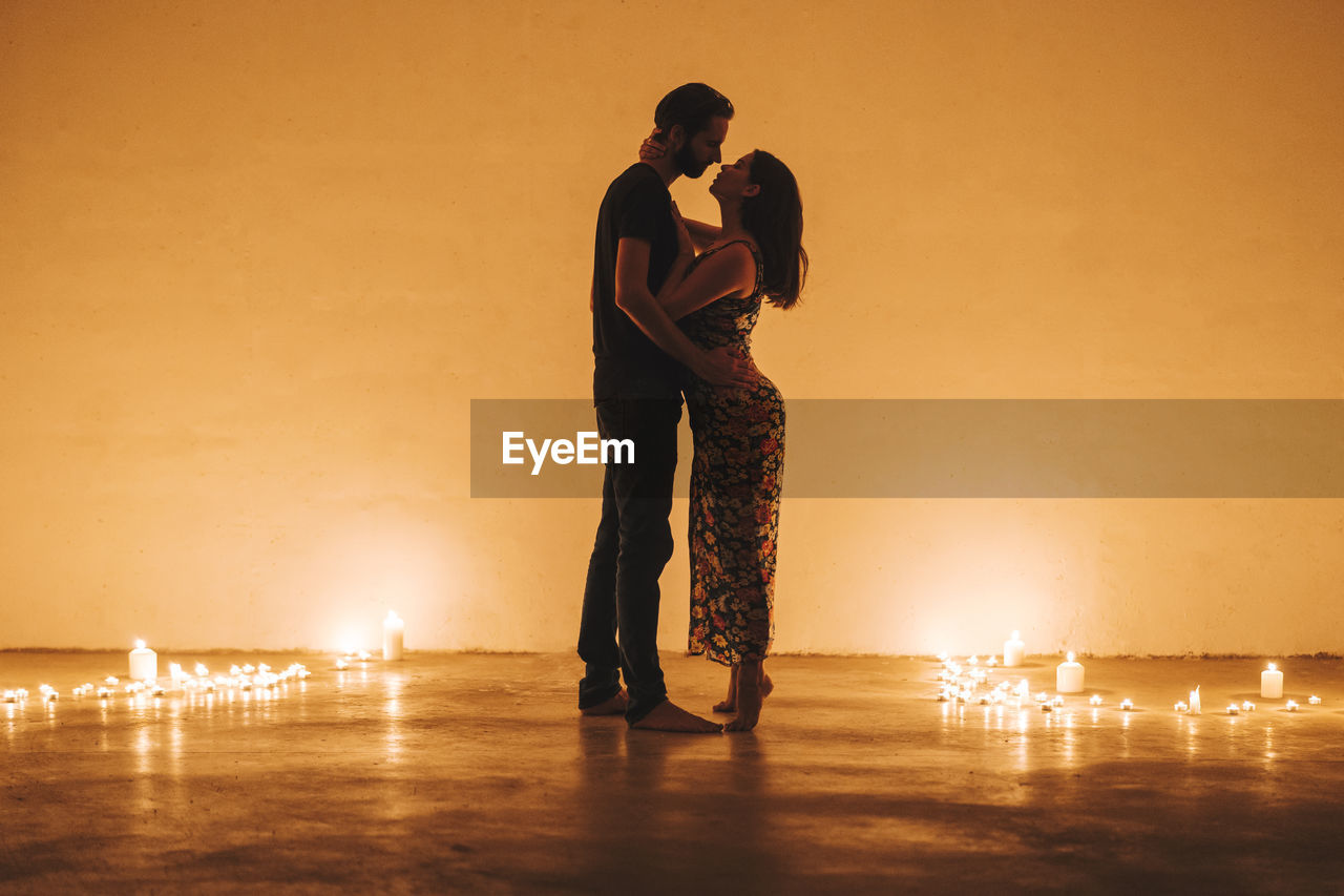 MAN AND WOMAN STANDING AGAINST ILLUMINATED ORANGE SKY