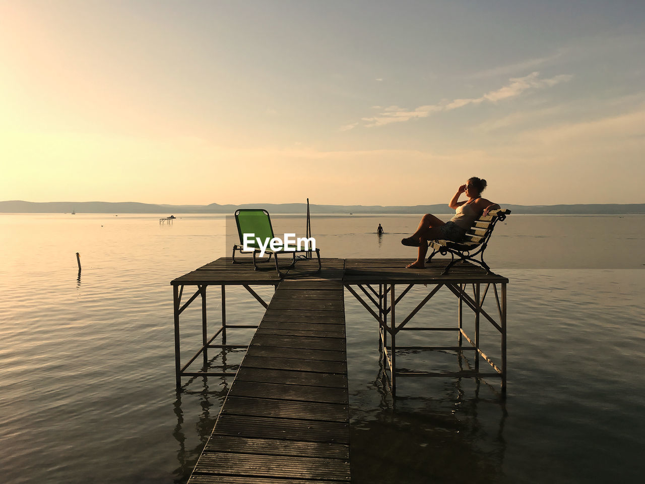 Woman sitting on bench over jetty in sea against sky during sunset
