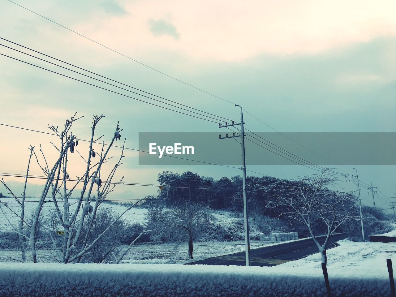 Low angle view of electric pole on snow covered field against cloudy sky