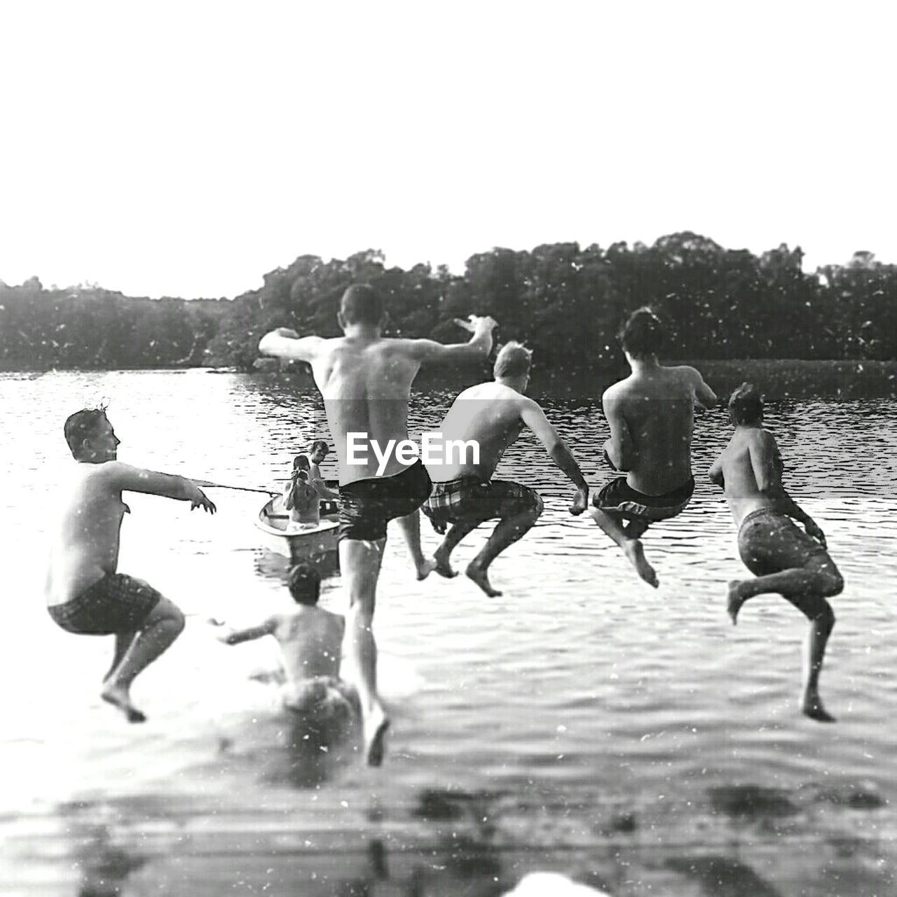 Shirtless Friends Jumping In Lake Against Sky