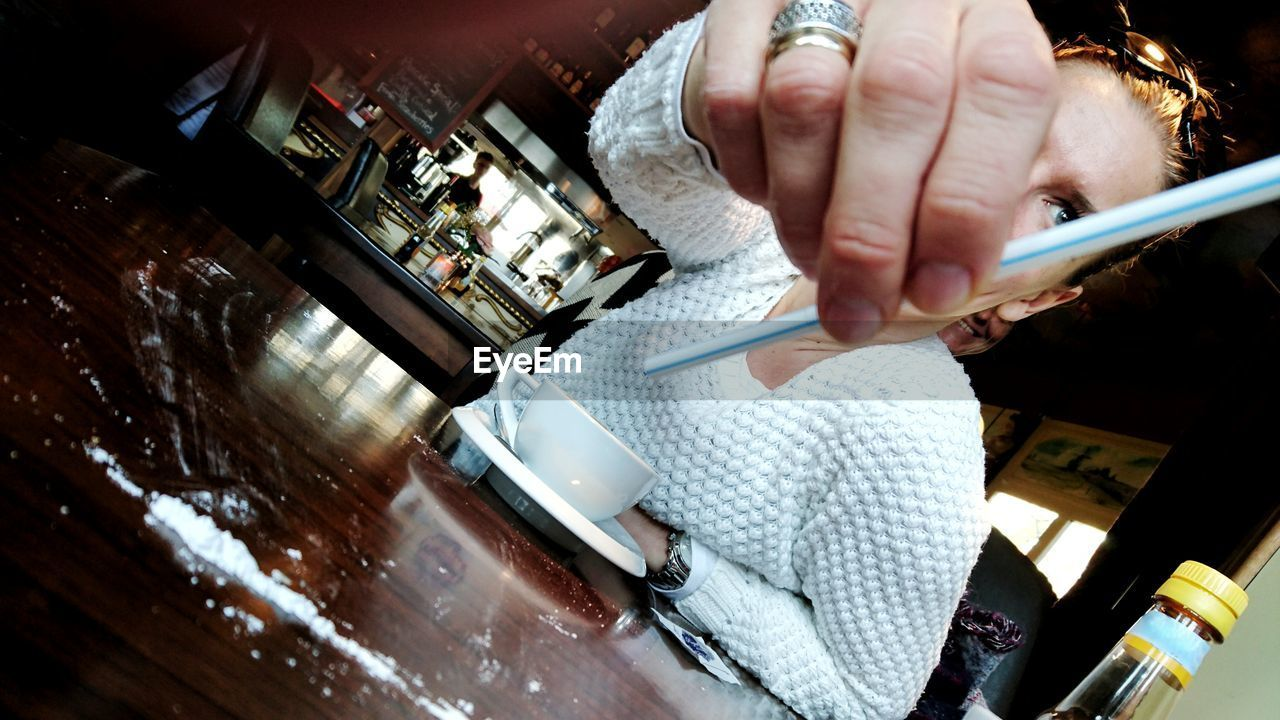 Close-up of woman holding drinking straw while sitting at cafe