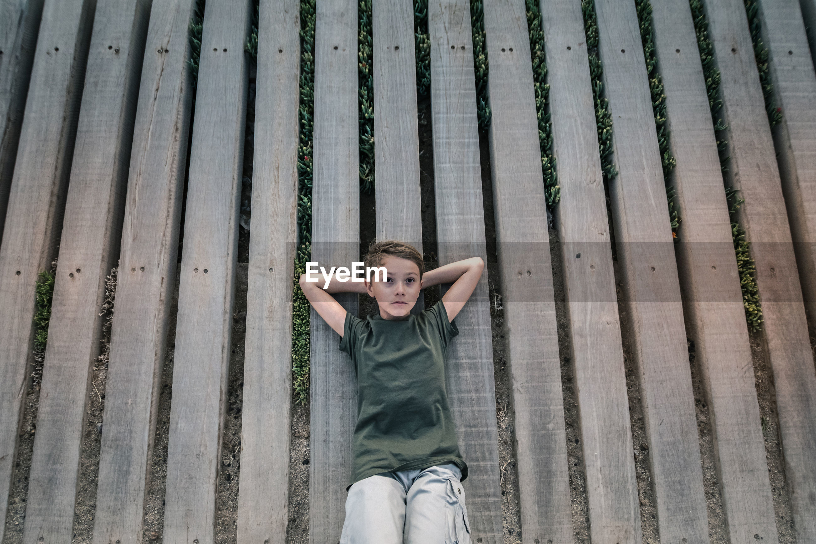 High angle view of boy lying on wooden planks