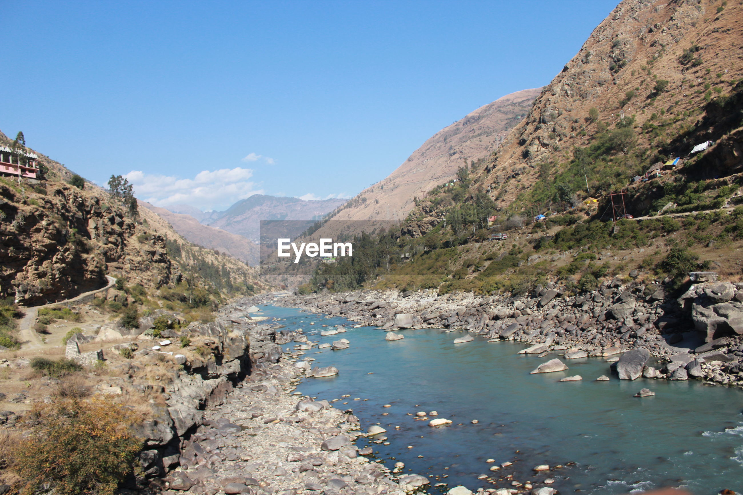 SCENIC VIEW OF RIVER AMIDST ROCKY MOUNTAINS AGAINST SKY