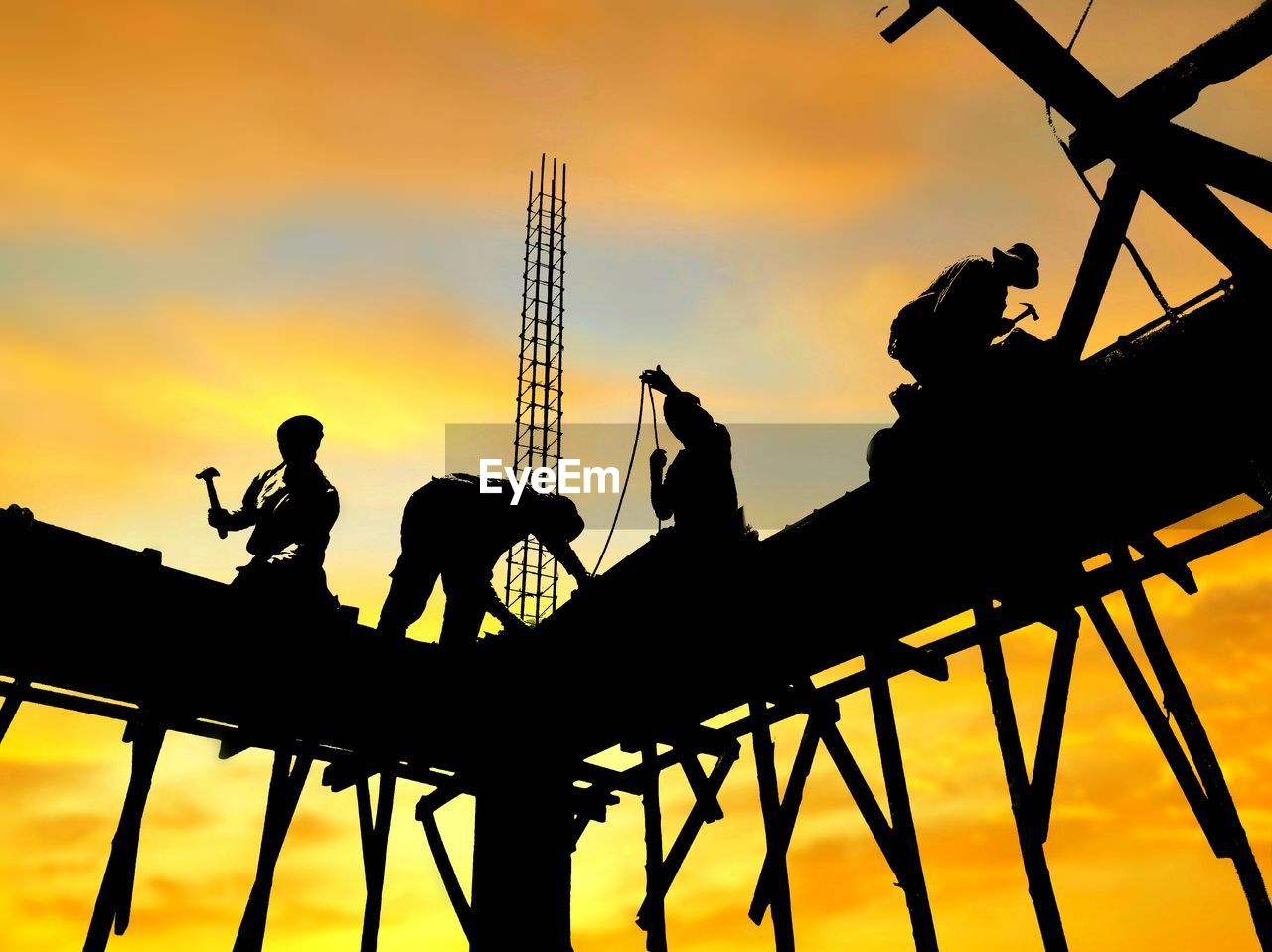 sunset, silhouette, sky, orange color, group of people, cloud - sky, real people, nature, construction industry, construction site, men, low angle view, industry, architecture, outdoors, machinery, development, built structure, occupation