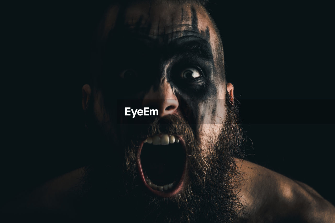 Portrait of a viking warrior with black war paint, screaming with rage and anger
