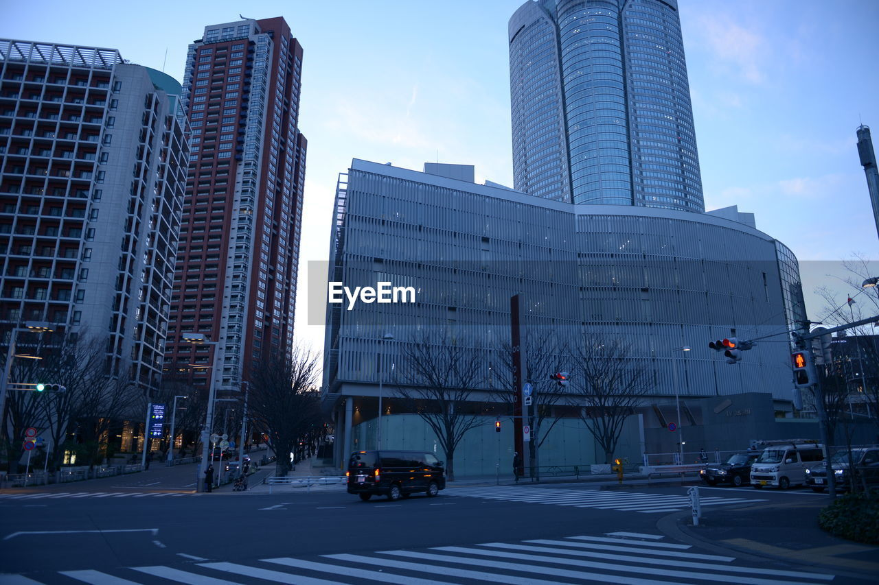 city, building exterior, architecture, built structure, street, transportation, building, motor vehicle, mode of transportation, car, office building exterior, sky, road, office, modern, land vehicle, tall - high, skyscraper, city street, sign, no people, light, outdoors