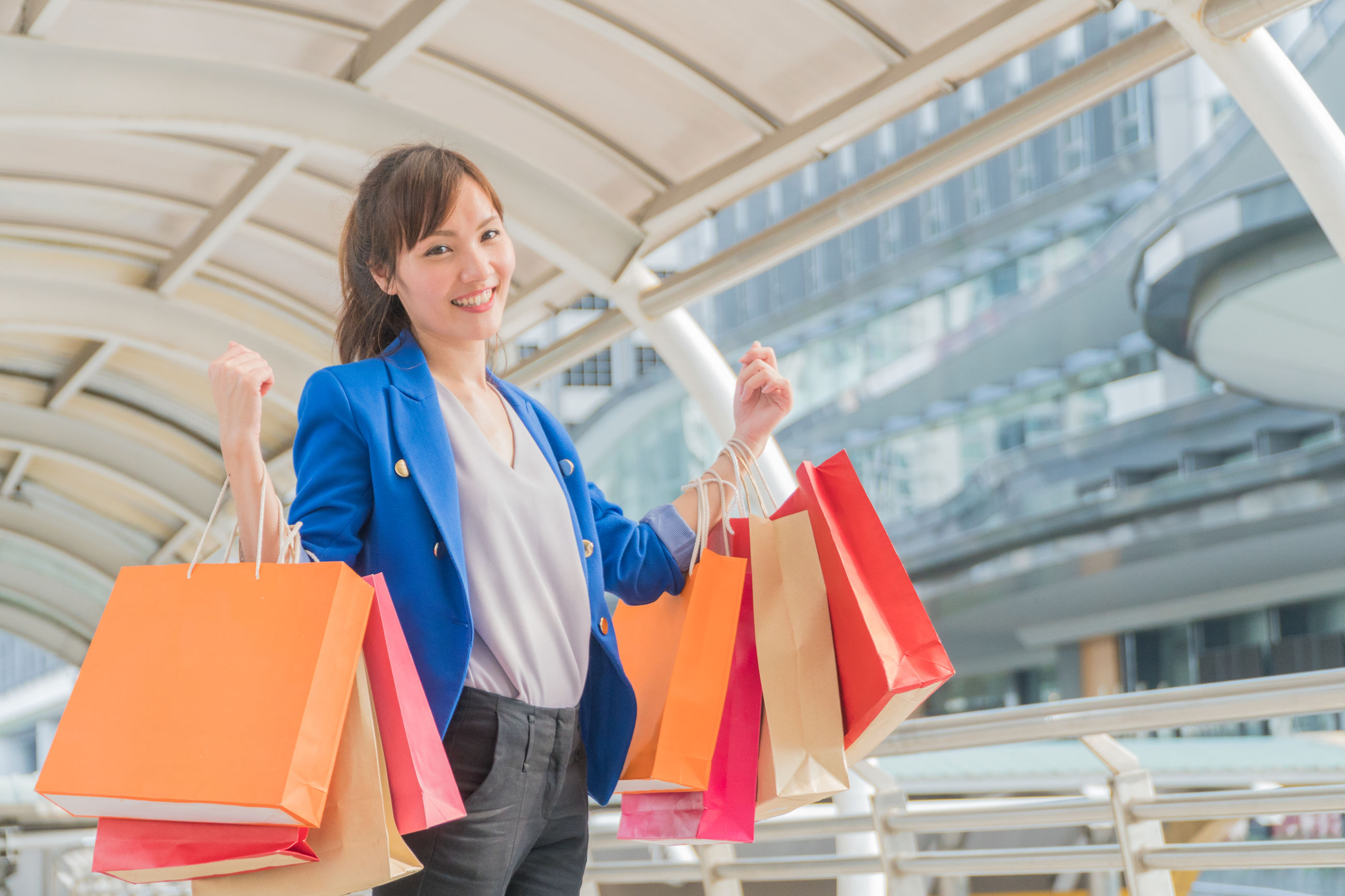 Portrait of smiling woman holding shopping bags while standing on footbridge in city
