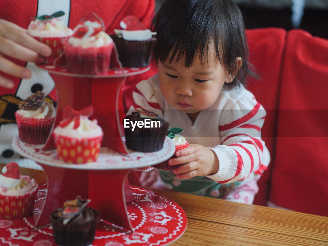 Baby Girl Having Cupcake At Table