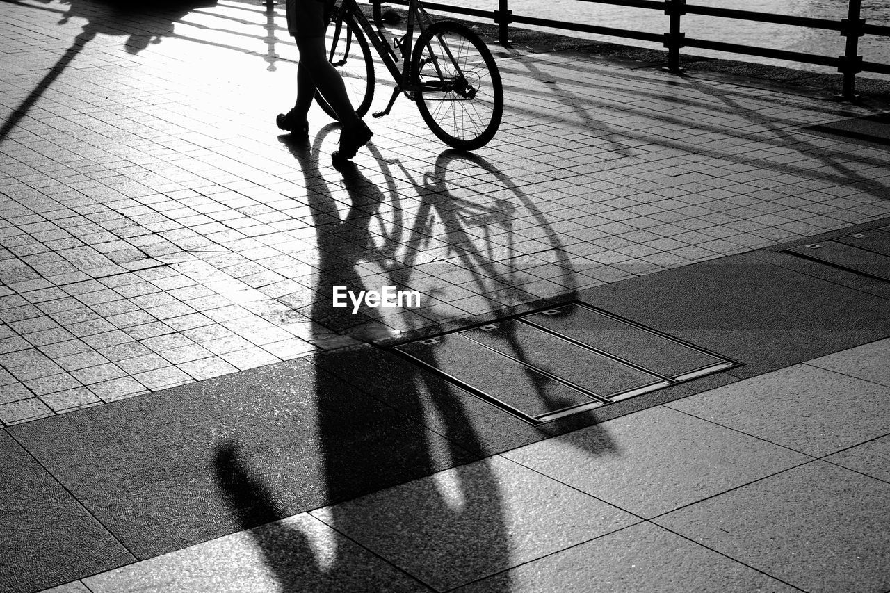 Low Section Of Person With Bicycle Walking On Street During Sunny Day
