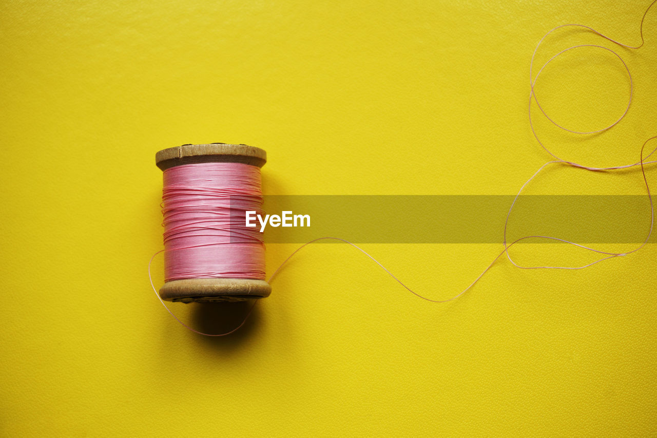 High Angle View Of Thread Spool Over Yellow Background