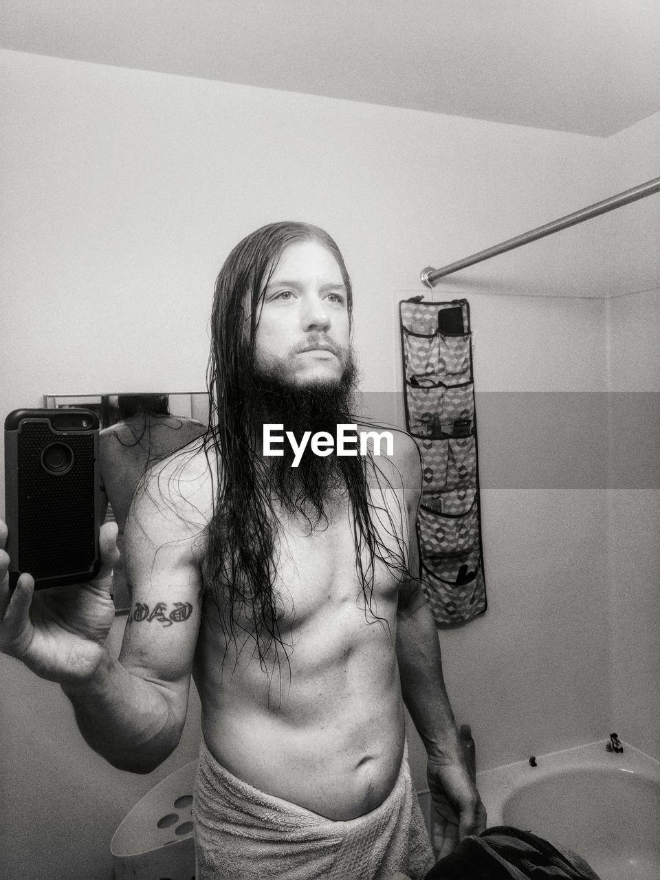 Shirtless man photographing at home