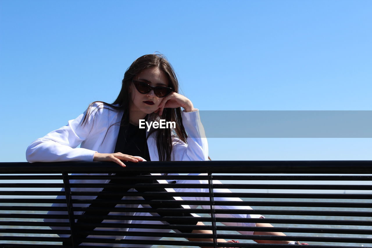 Confident girl sitting by railing against clear blue sky