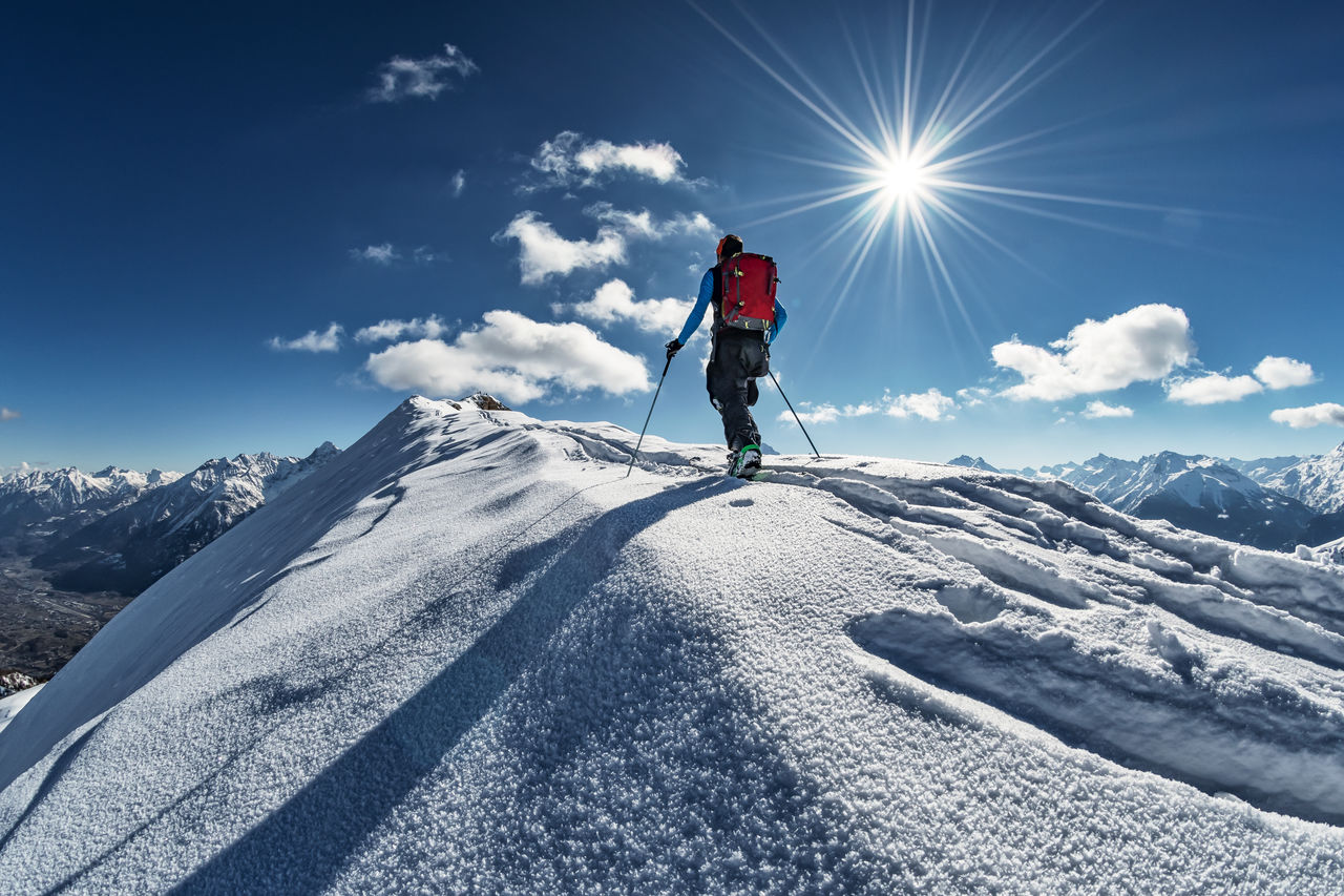 MAN STANDING ON SNOWCAPPED MOUNTAINS AGAINST SKY