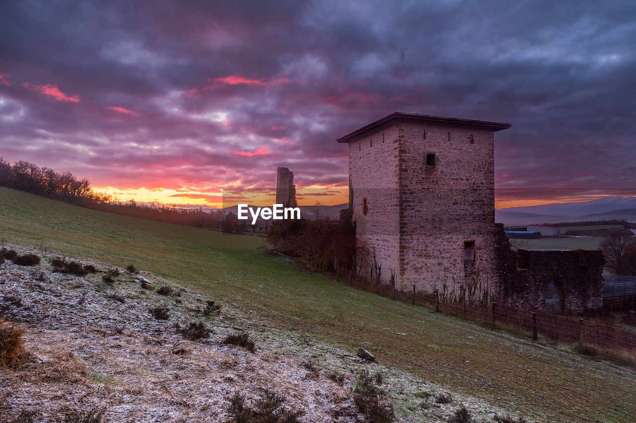 architecture, cloud - sky, built structure, sky, building exterior, sunset, building, history, the past, nature, no people, land, field, grass, beauty in nature, scenics - nature, environment, orange color, plant, dusk, outdoors, ruined