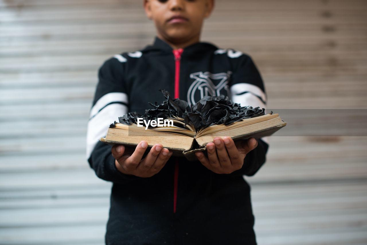 Conceptual Portrait Of A Boy Holding A Burnt Book