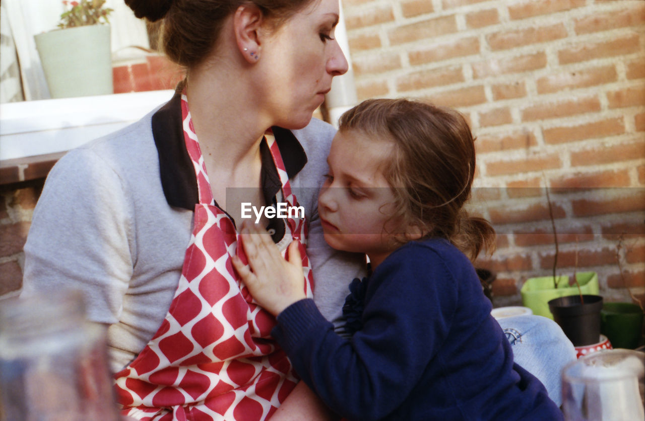 Woman With Daughter Sitting At Home