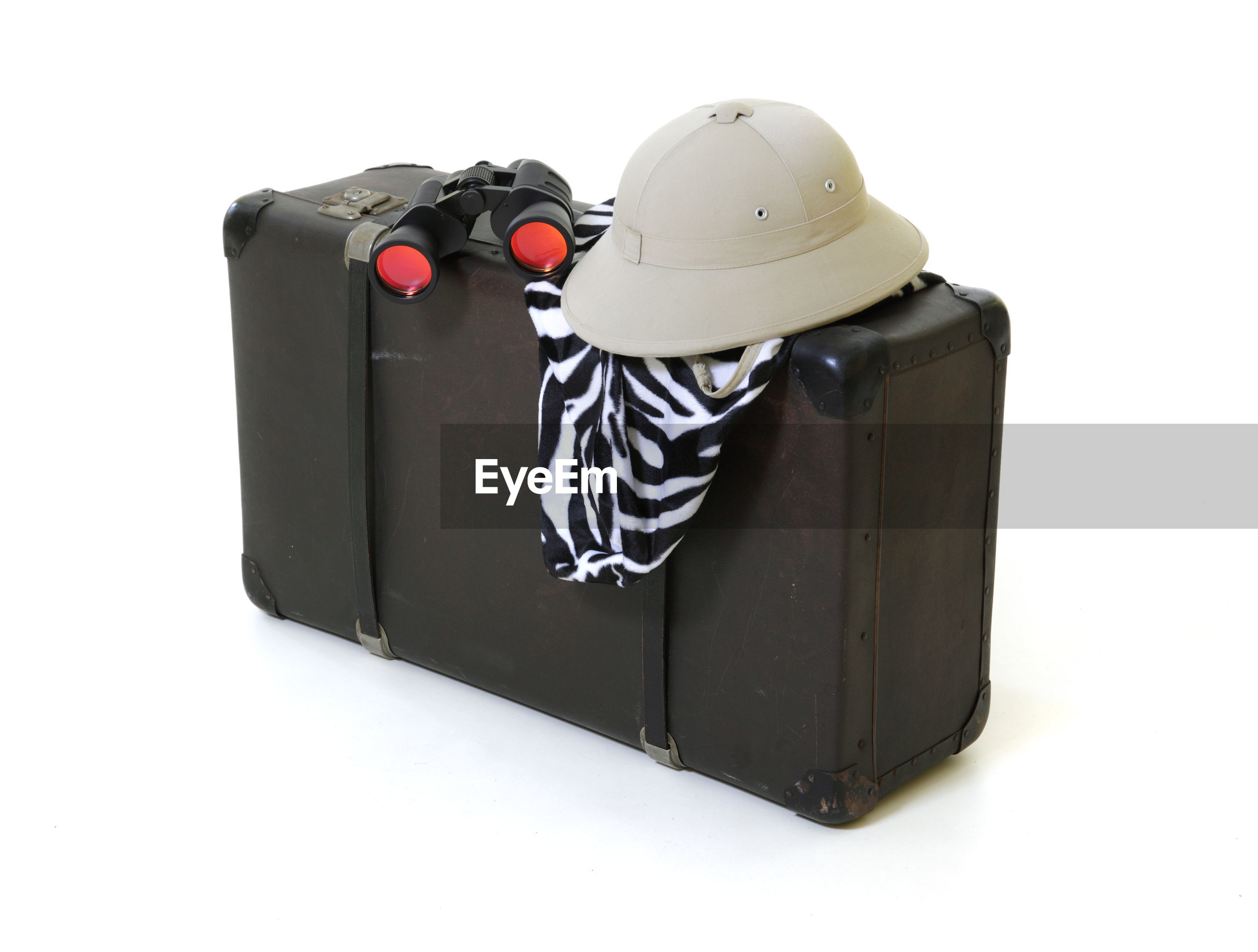 Close-up of luggage with hat and binoculars against white background