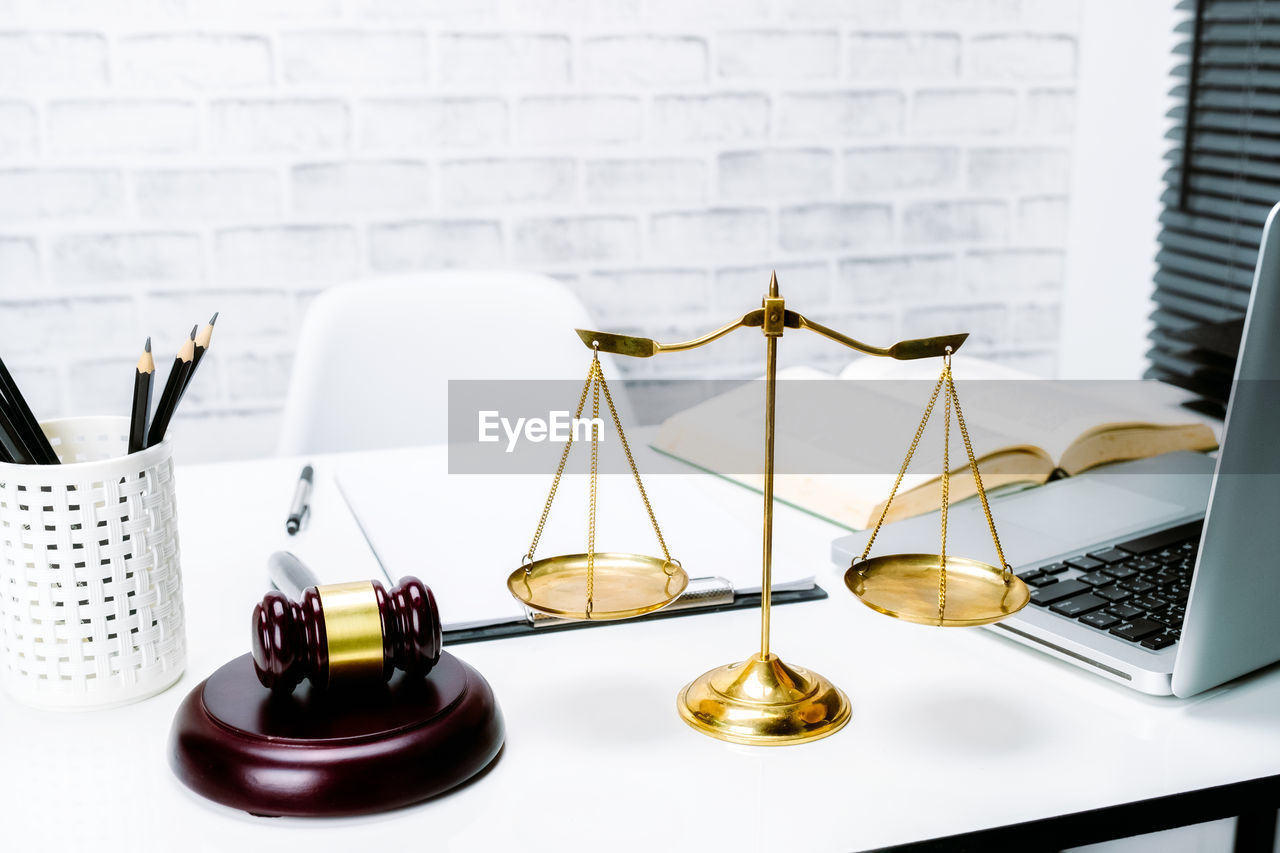 table, no people, indoors, still life, laptop, business, technology, close-up, justice - concept, wireless technology, weight scale, gold colored, computer, white background, publication, choice, furniture, communication, connection