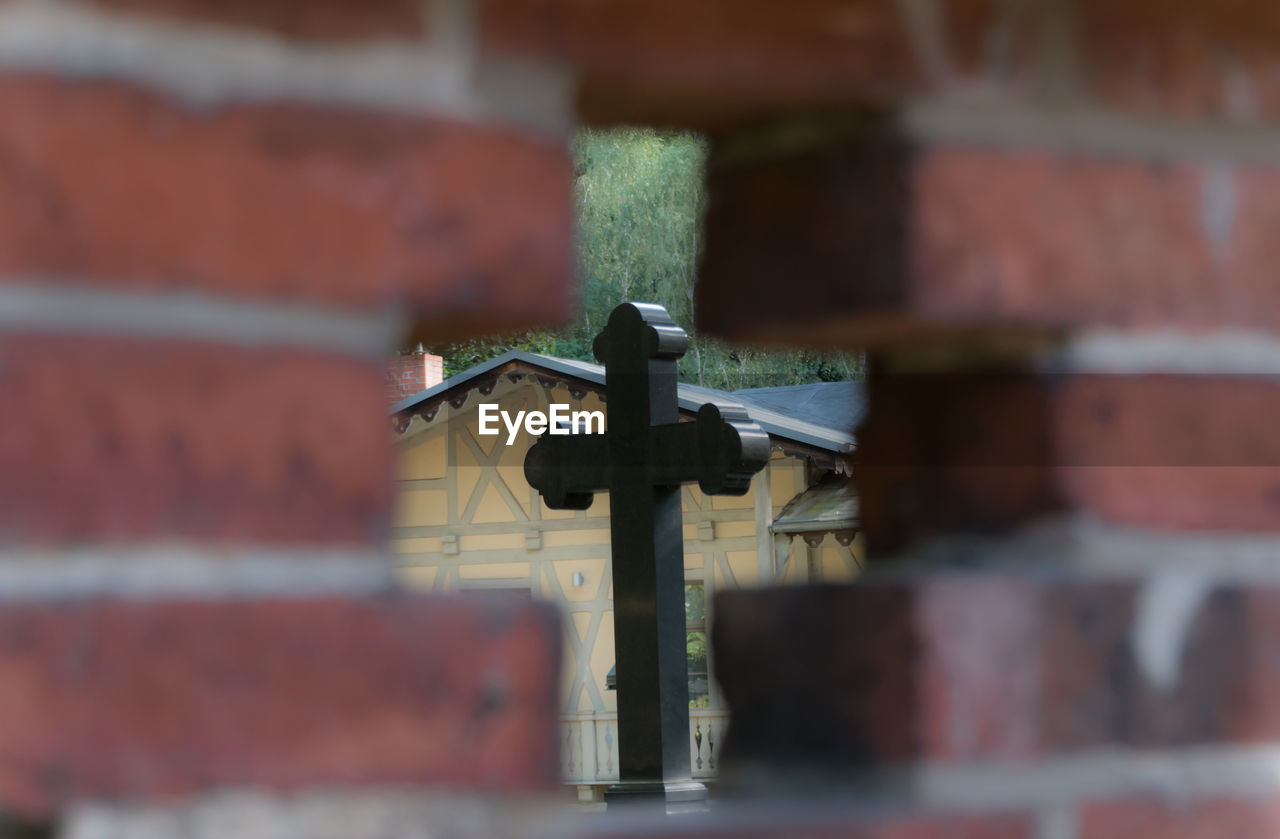 Cross Seen Through Hole On Brick Wall