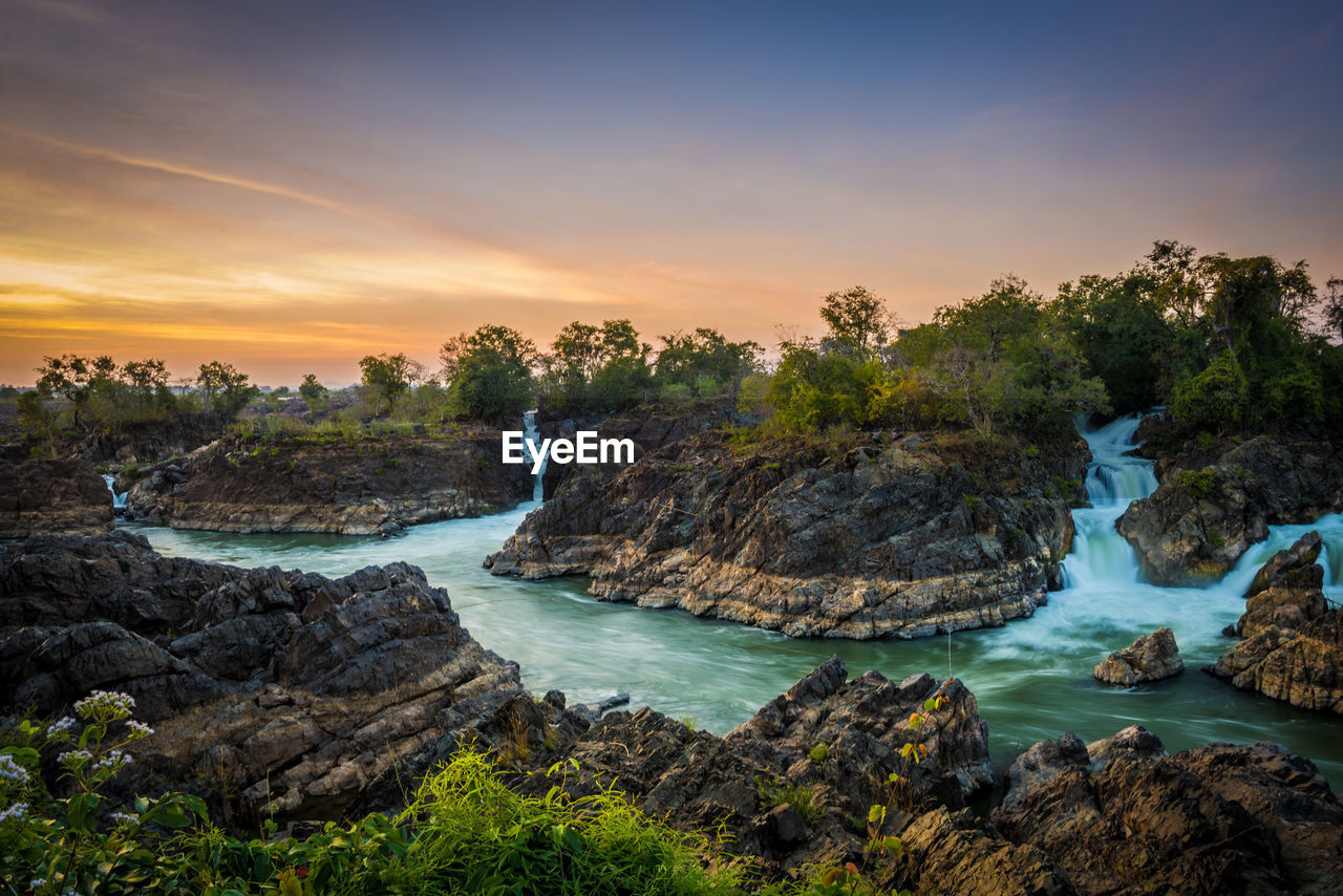 water, sunset, beauty in nature, scenics - nature, rock, sky, solid, rock - object, tranquility, tranquil scene, nature, plant, non-urban scene, idyllic, cloud - sky, sea, land, no people, rock formation, outdoors, flowing water