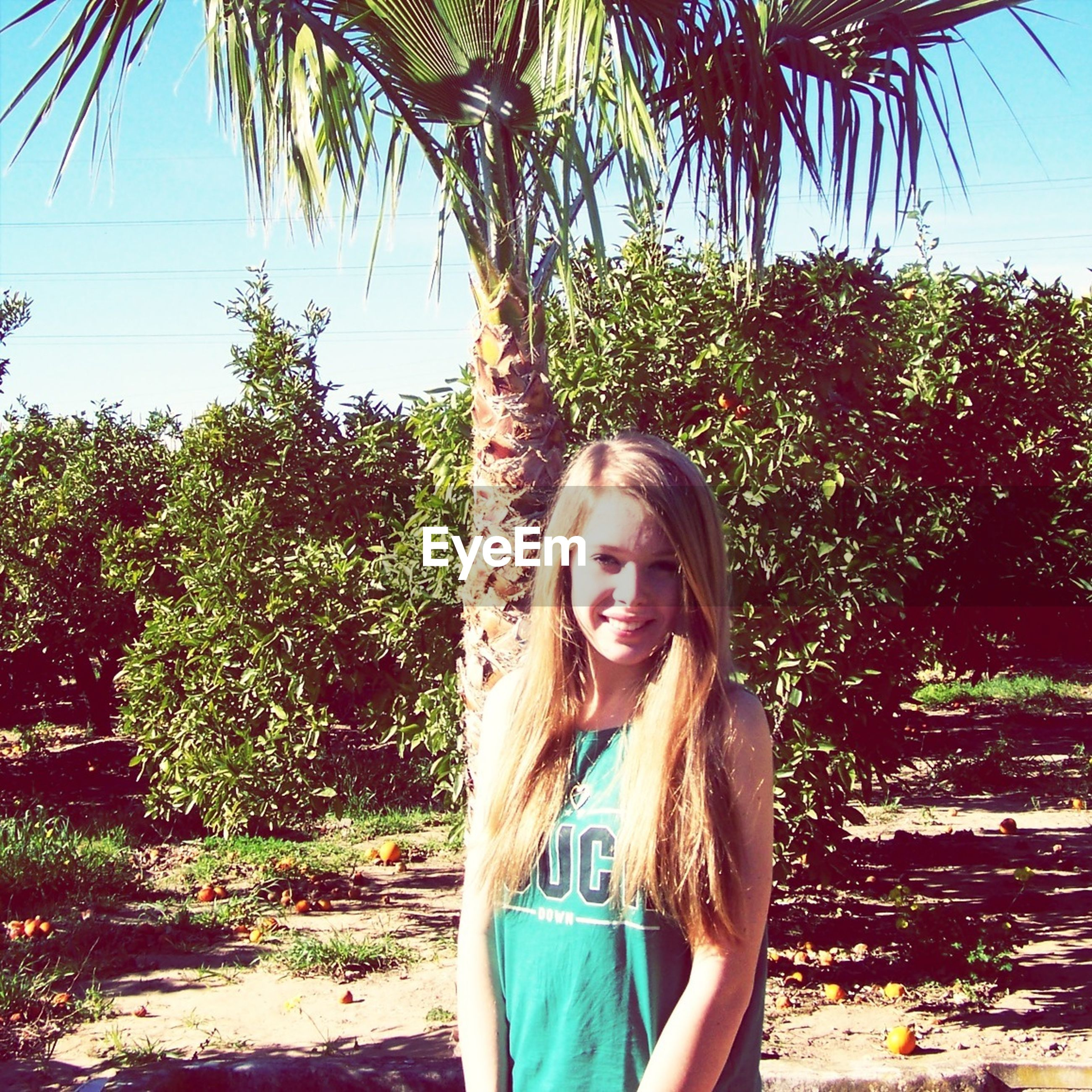 young adult, tree, young women, lifestyles, person, leisure activity, long hair, casual clothing, looking at camera, standing, clear sky, front view, portrait, sunlight, smiling, growth, three quarter length