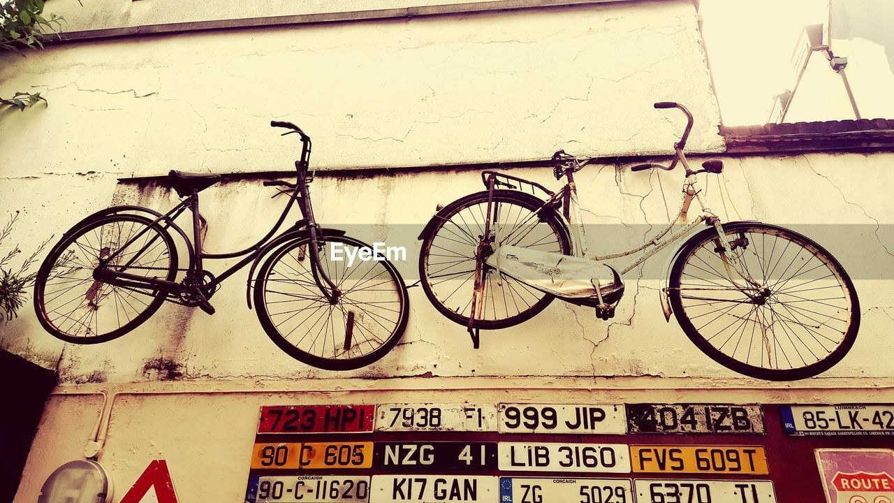 bicycle, transportation, mode of transportation, land vehicle, no people, stationary, built structure, communication, building exterior, wall - building feature, architecture, day, text, outdoors, wall, sign, parking, wheel, hanging, western script