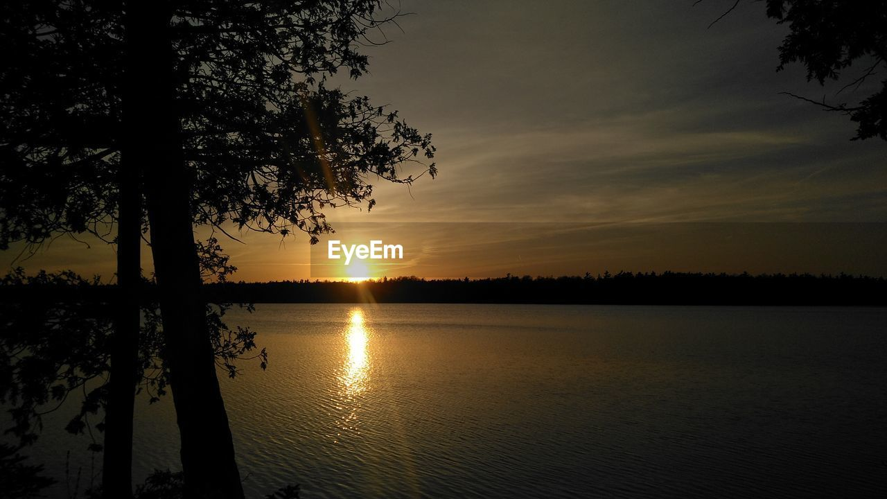 sky, sunset, beauty in nature, tree, scenics - nature, tranquility, tranquil scene, water, silhouette, plant, reflection, sun, idyllic, orange color, nature, no people, lake, non-urban scene, cloud - sky, outdoors
