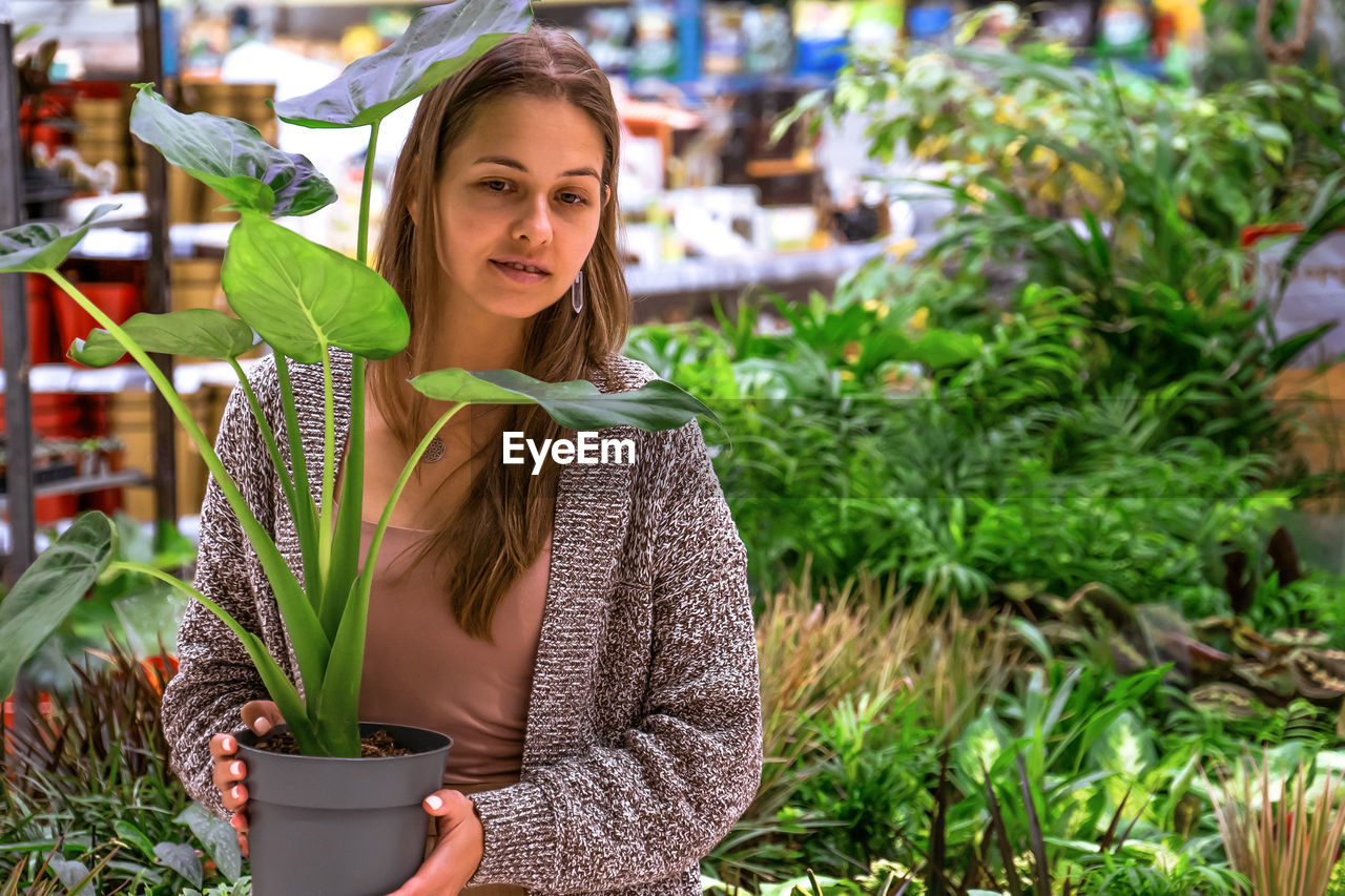 Young woman holding a pot with monstera in the middle of a flower store.