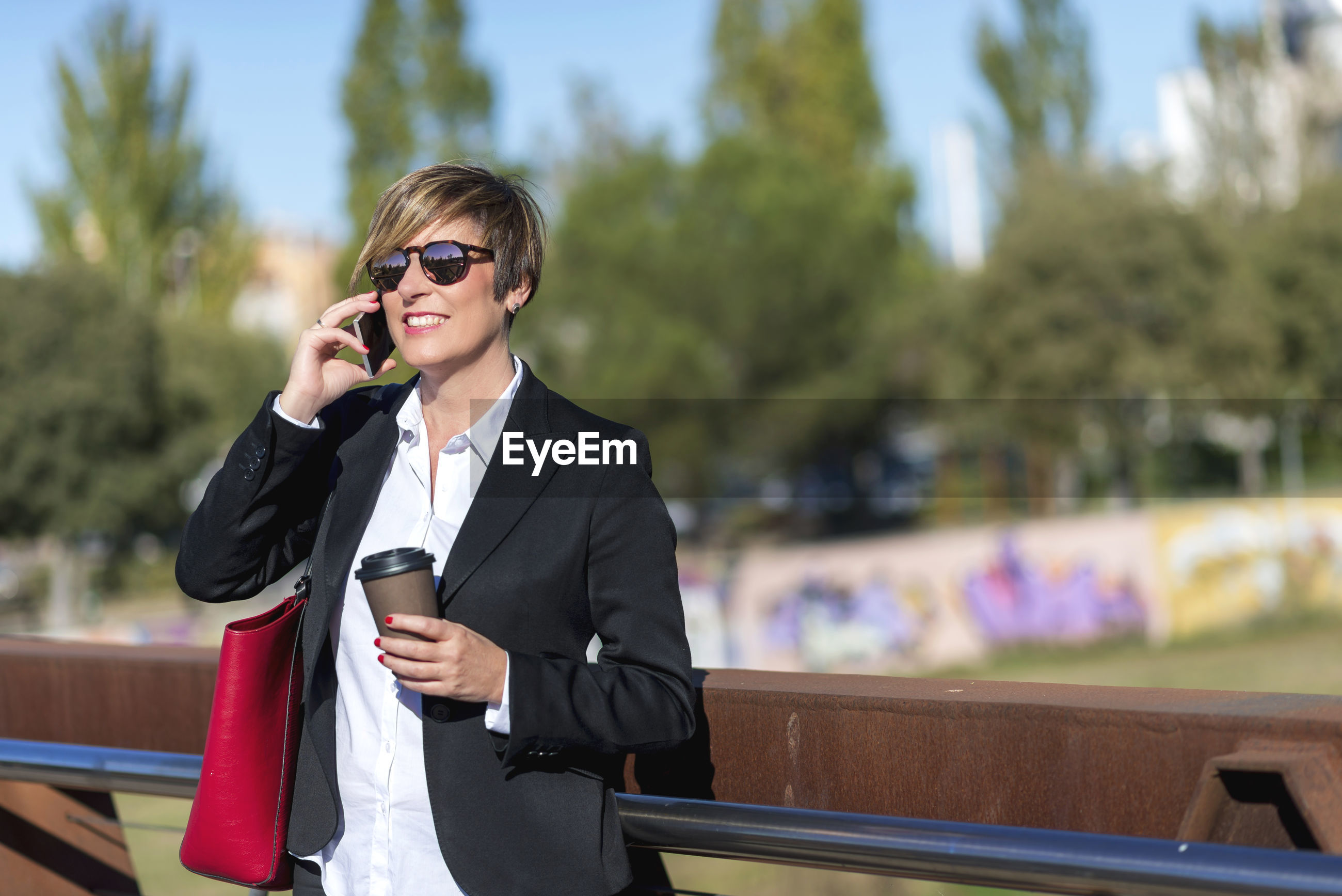 Smiling businesswoman talking on mobile phone while standing in city