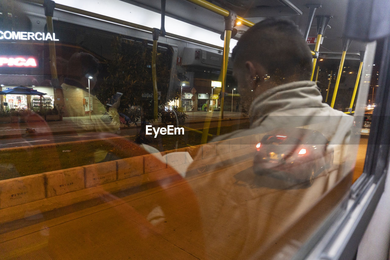 transportation, mode of transportation, motion, real people, illuminated, glass - material, blurred motion, one person, land vehicle, night, transparent, men, public transportation, reflection, architecture, city, lifestyles, travel, rear view, outdoors