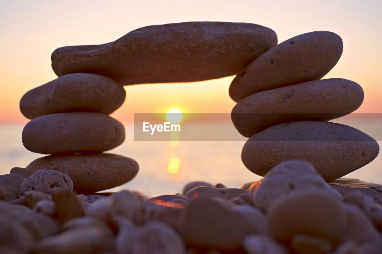 Sunset Seen Through Stack Of Pebbles