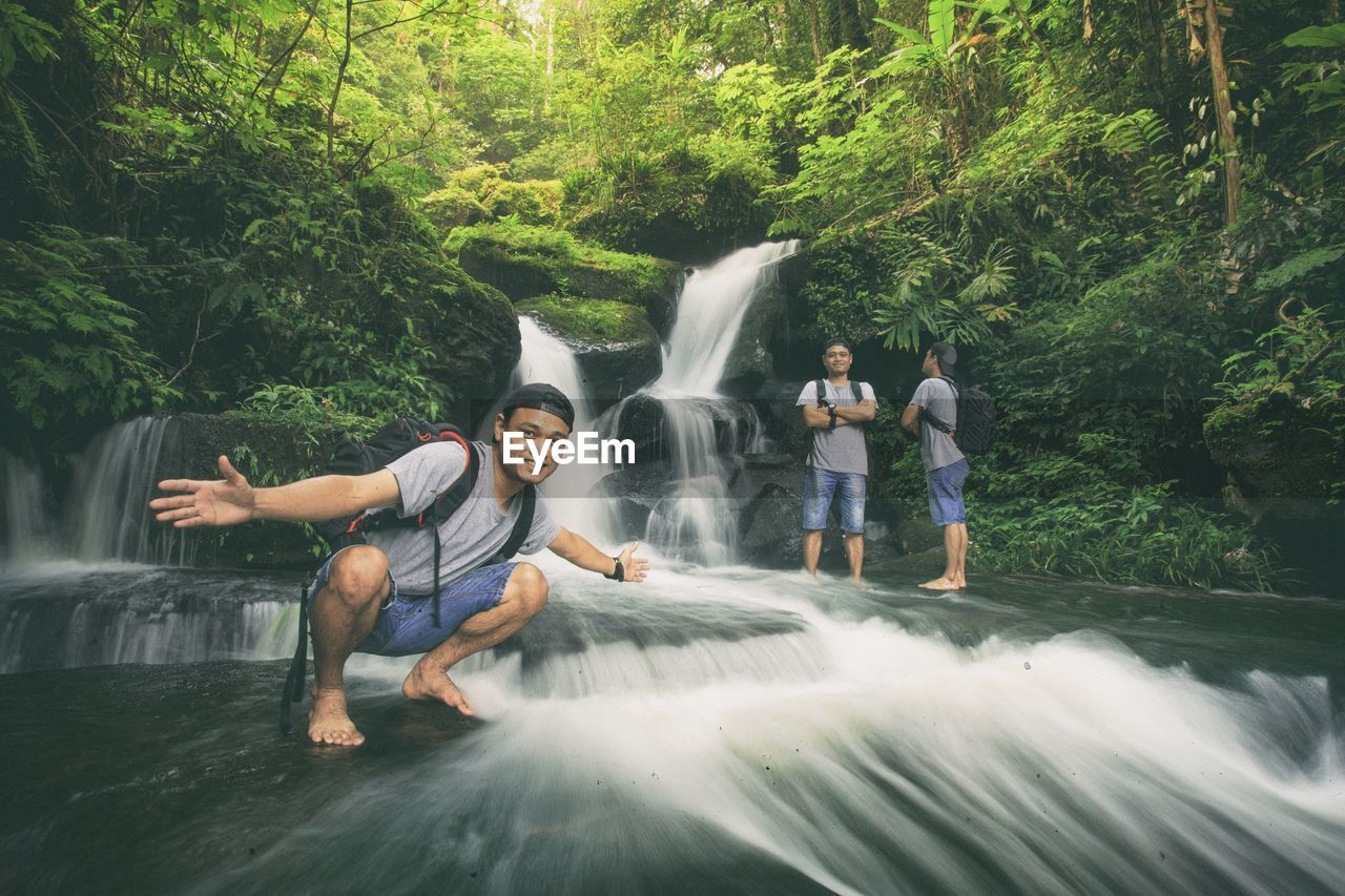 Multiple Image Of Man By Waterfall In Forest