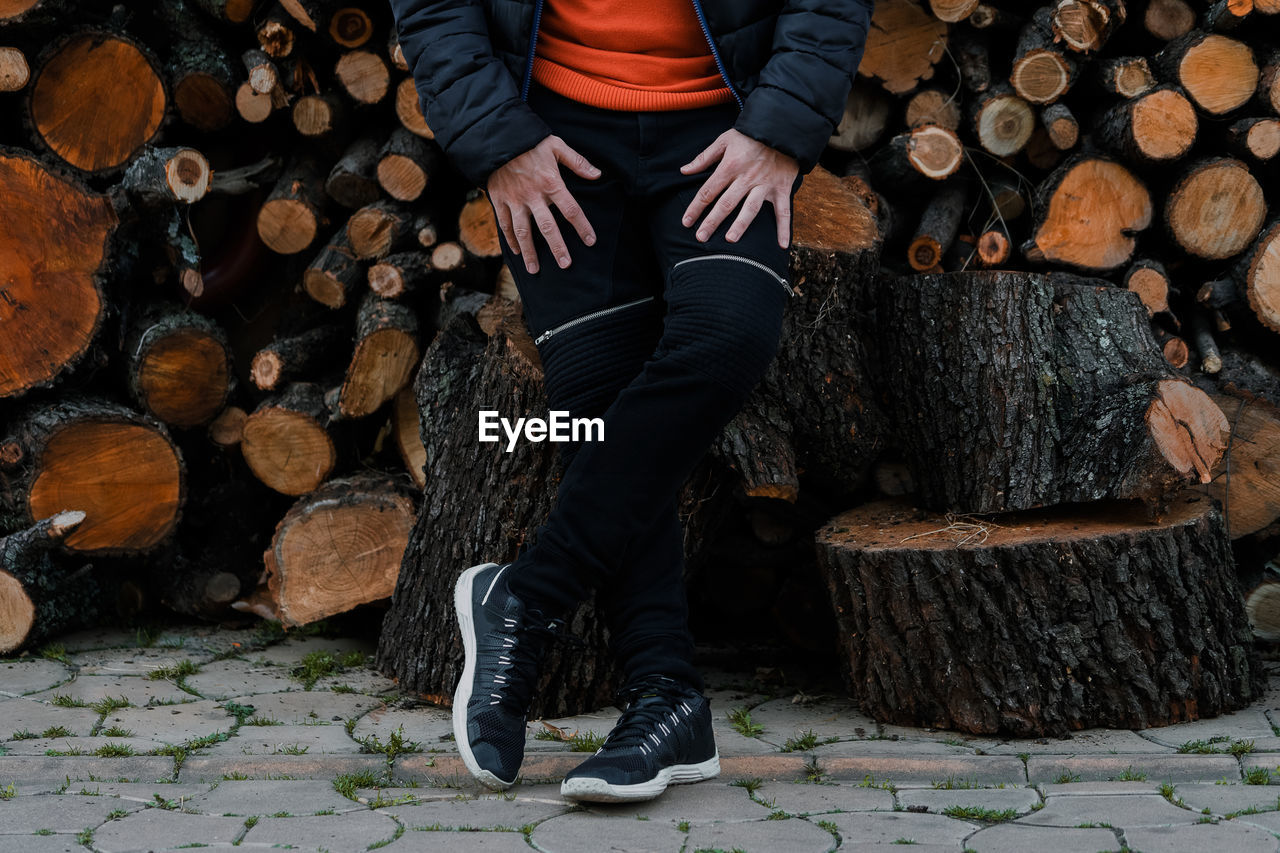 Low Section Of Man Sitting On Log