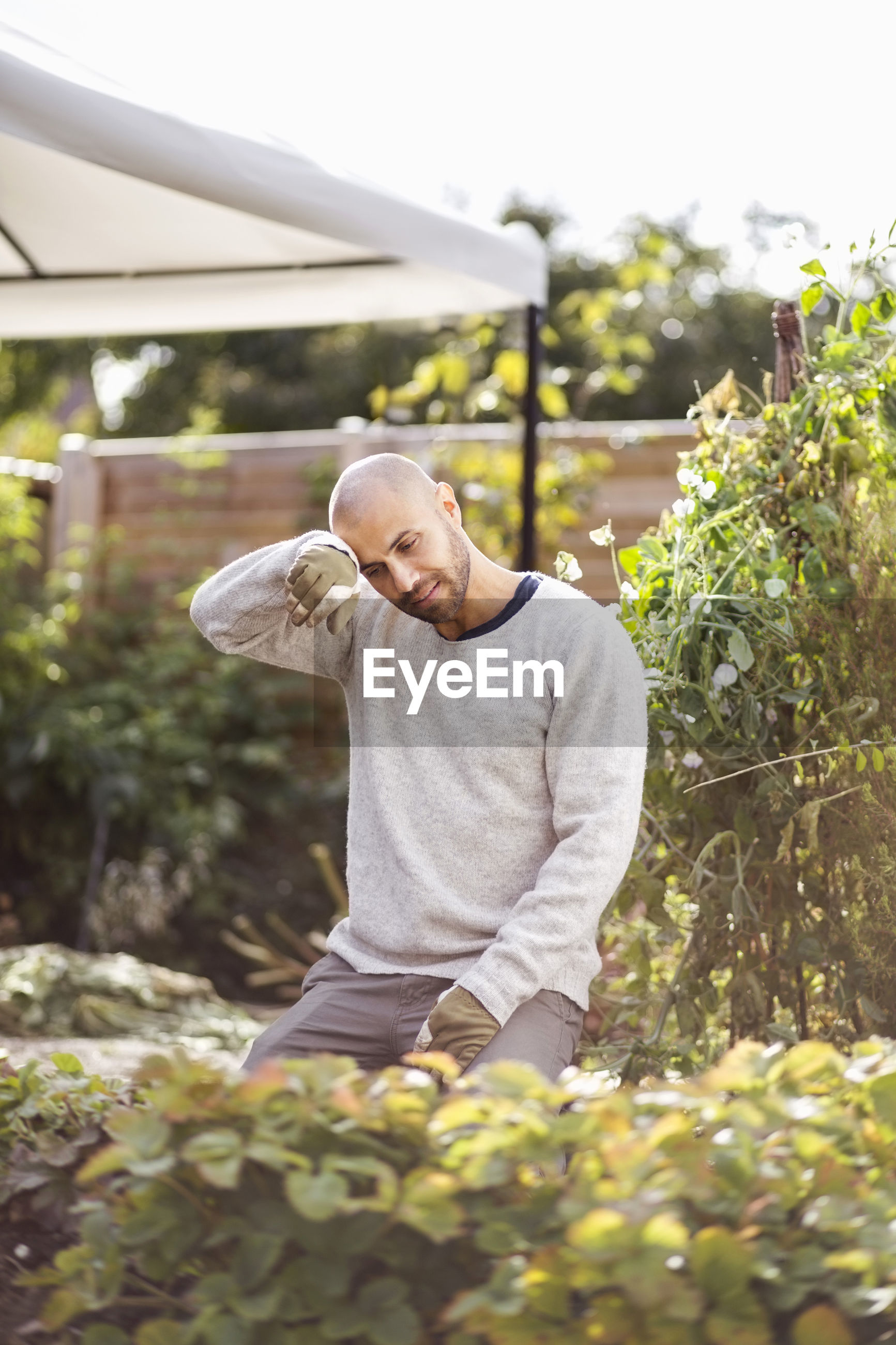 FULL LENGTH PORTRAIT OF MAN STANDING AGAINST PLANTS