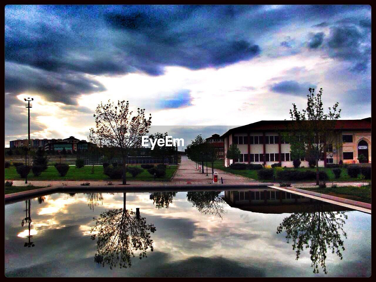 sky, reflection, cloud - sky, cloud, water, architecture, building exterior, tree, built structure, outdoors, no people, nature, puddle, day, beauty in nature, city