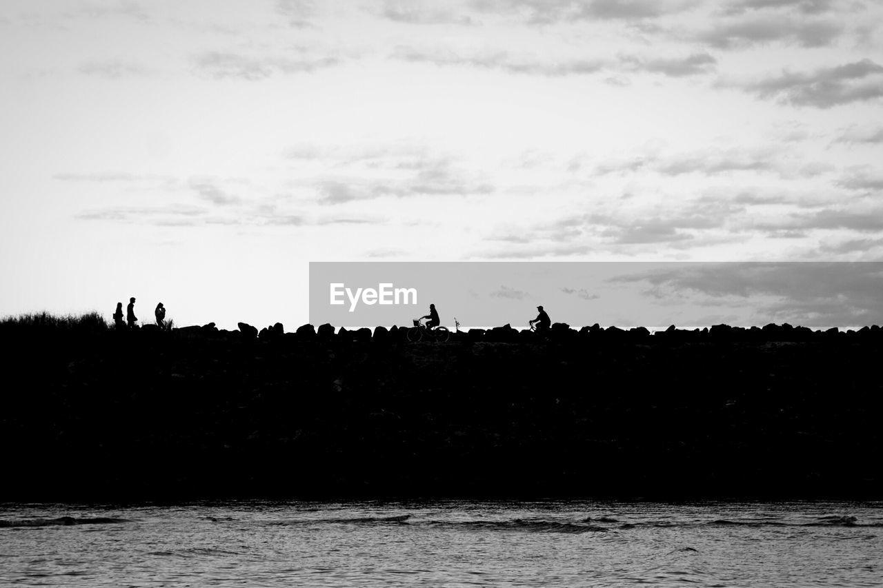 Silhouette people on groyne against sky