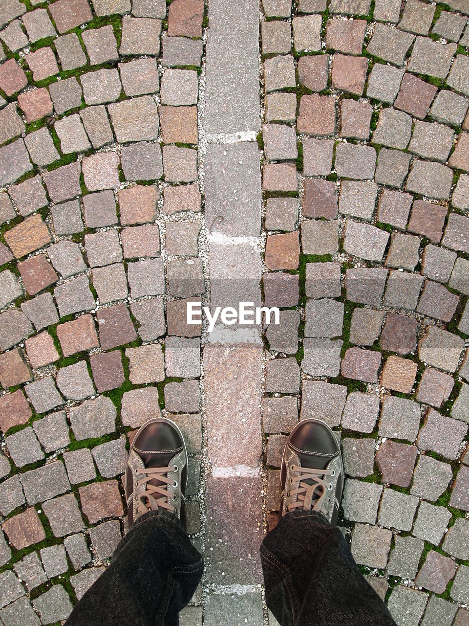 Low Section Of Man Standing On Cobblestone Floor