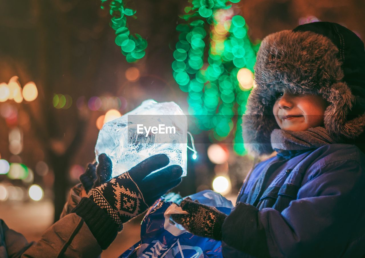 Portrait Of Smiling Boy Looking At Ice Chunk At Night