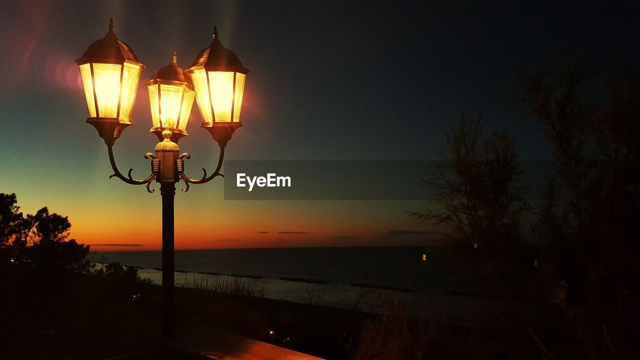lighting equipment, sky, illuminated, street light, street, no people, night, sunset, electric light, light, tree, nature, beauty in nature, plant, water, glowing, orange color, scenics - nature, silhouette, outdoors, electricity, dark, electric lamp