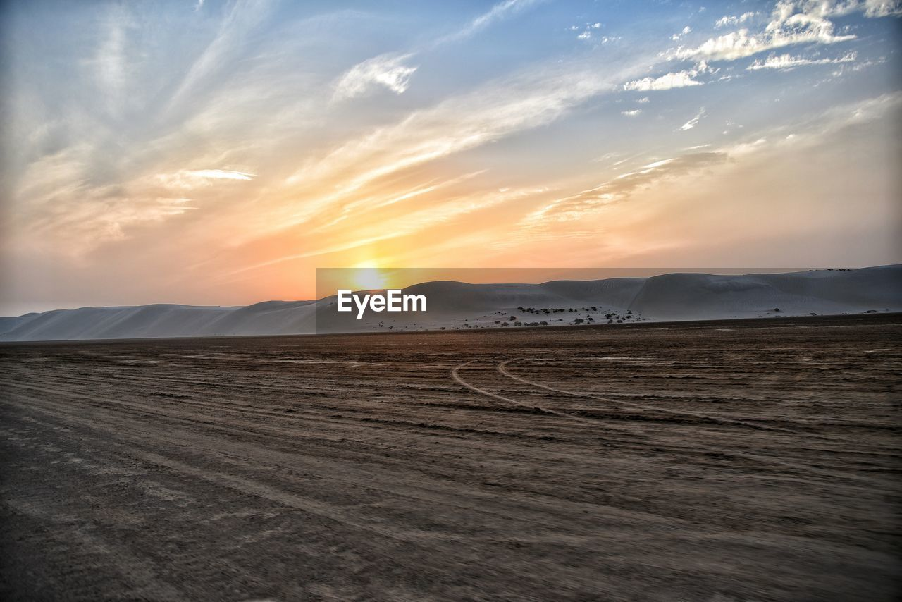 sky, scenics - nature, sunset, beauty in nature, tranquil scene, cloud - sky, environment, land, tranquility, landscape, non-urban scene, mountain, no people, nature, idyllic, desert, sand, remote, outdoors, orange color, arid climate, climate