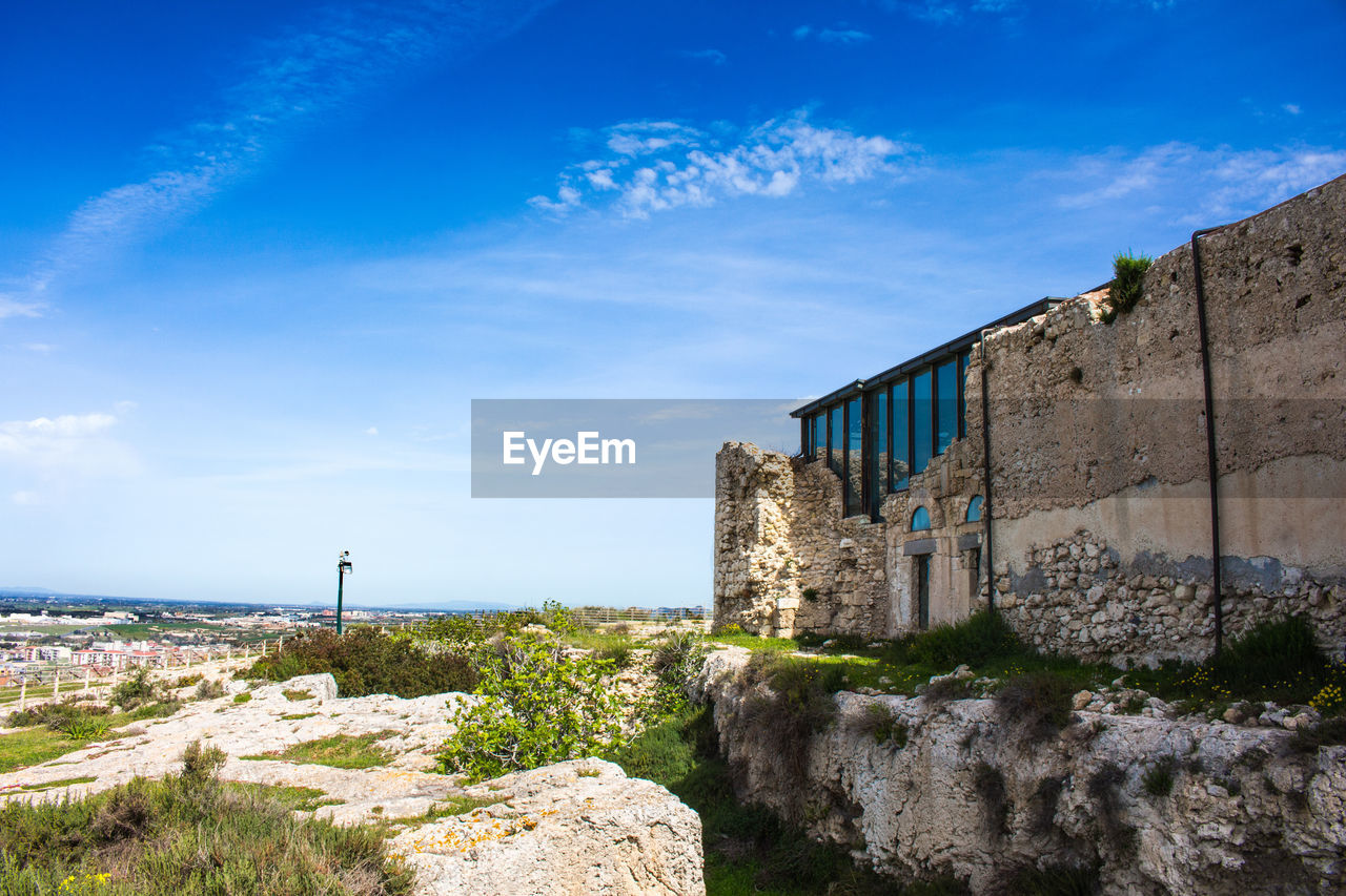 sky, architecture, built structure, cloud - sky, nature, building exterior, day, no people, blue, building, sunlight, plant, water, outdoors, solid, rock, land, beauty in nature, rock - object, wall