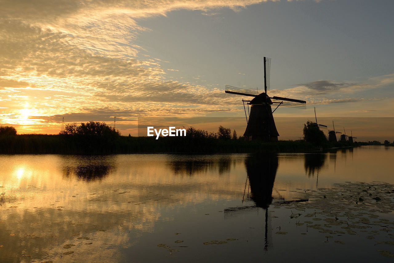 sunset, reflection, wind power, windmill, wind turbine, alternative energy, water, environmental conservation, traditional windmill, renewable energy, silhouette, sky, nature, scenics, beauty in nature, tranquil scene, no people, lake, cloud - sky, industrial windmill, tranquility, fuel and power generation, outdoors, architecture, tree, day