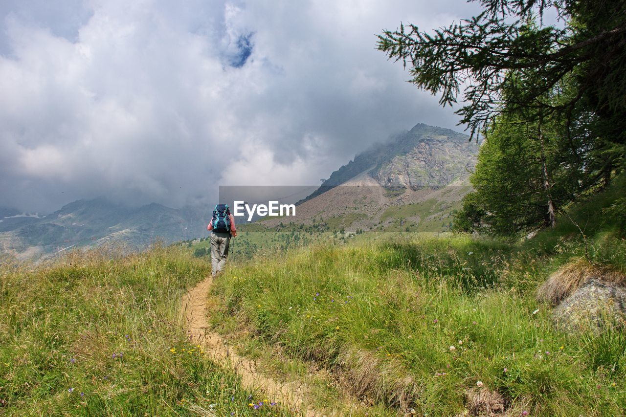 mountain, activity, plant, beauty in nature, men, scenics - nature, hiking, leisure activity, real people, transportation, grass, sky, cloud - sky, non-urban scene, day, nature, mountain range, rear view, walking, people, riding, outdoors