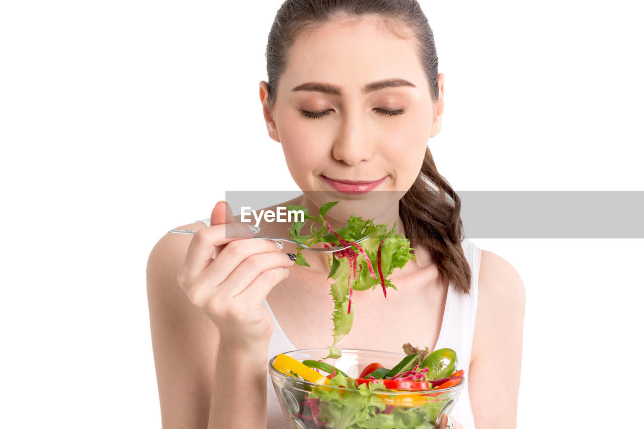 Young woman eating salad against white background