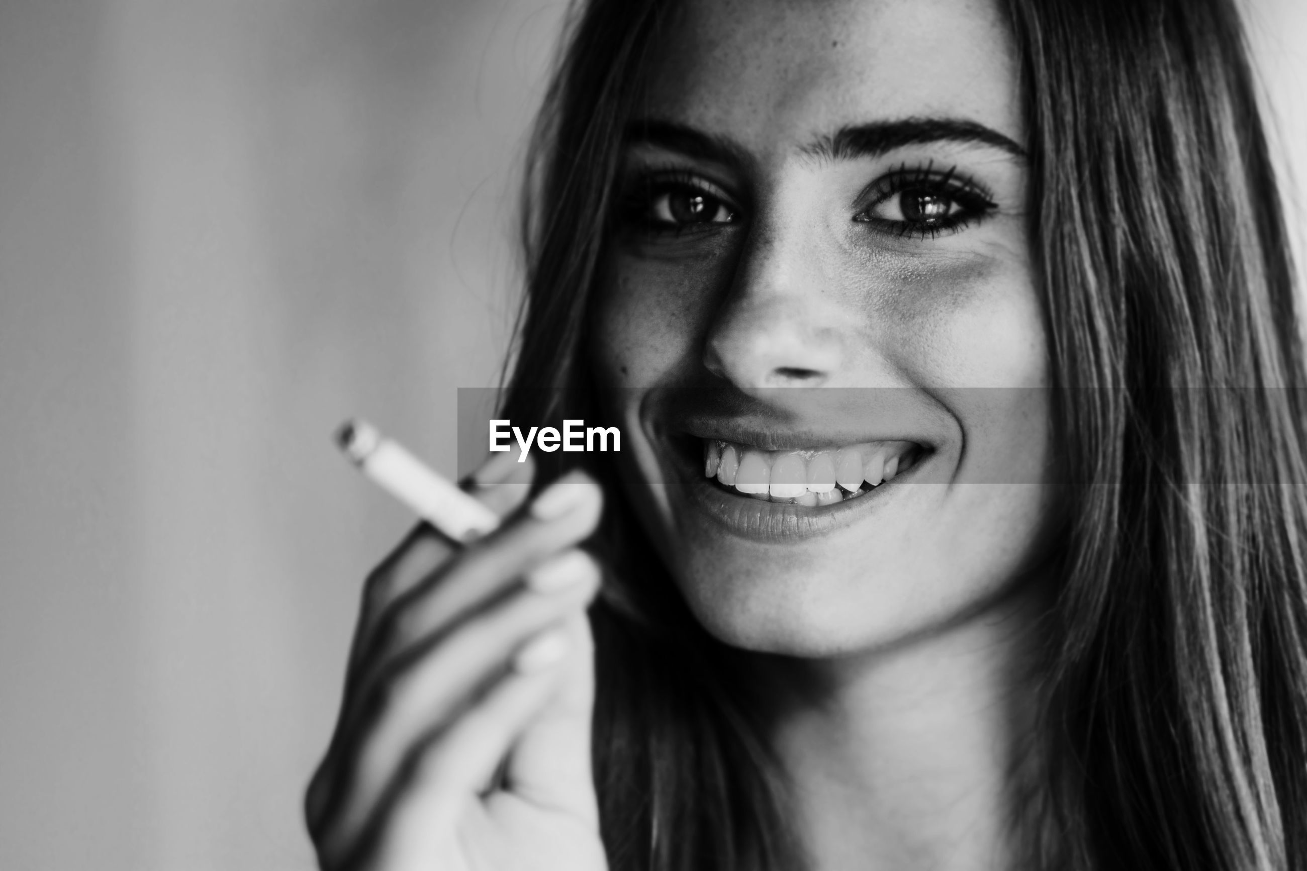 portrait, smiling, happiness, looking at camera, young adult, headshot, one person, emotion, teeth, close-up, front view, young women, toothy smile, real people, focus on foreground, indoors, cheerful, communication, cigarette, beautiful woman, human face