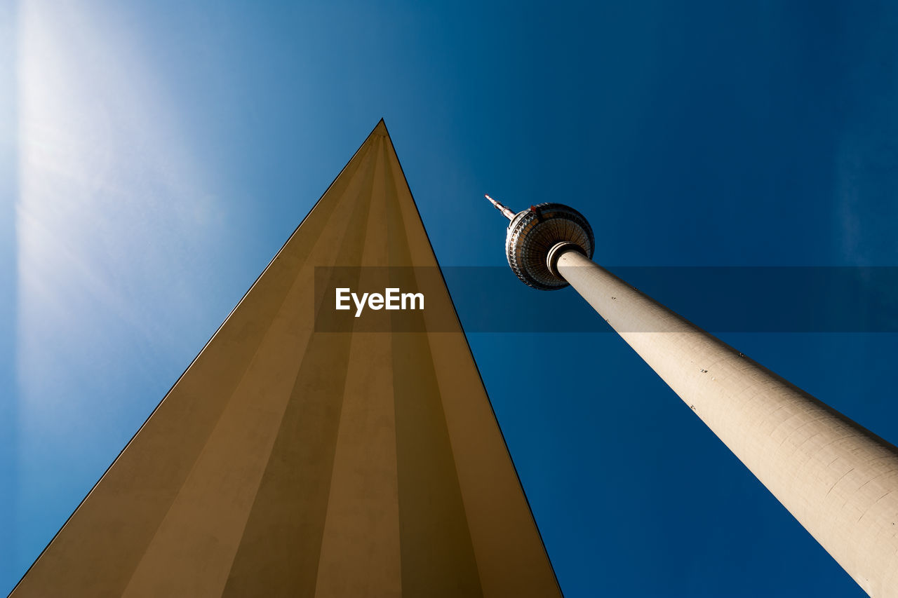 Low angle view of communications tower and building against blue sky